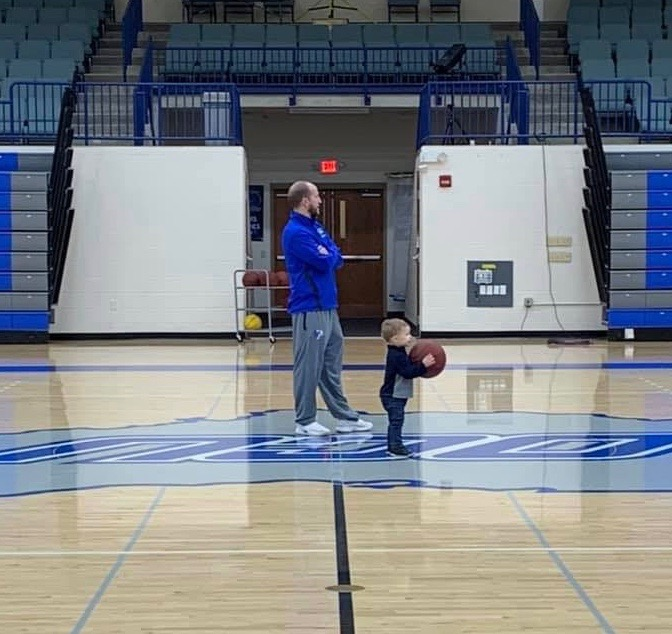 Little boy holding basketball with coach on court