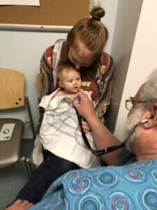 Mother holding baby while doctor listens with stethoscope