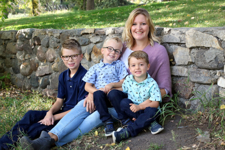 Mother with three sons smiling, color photo