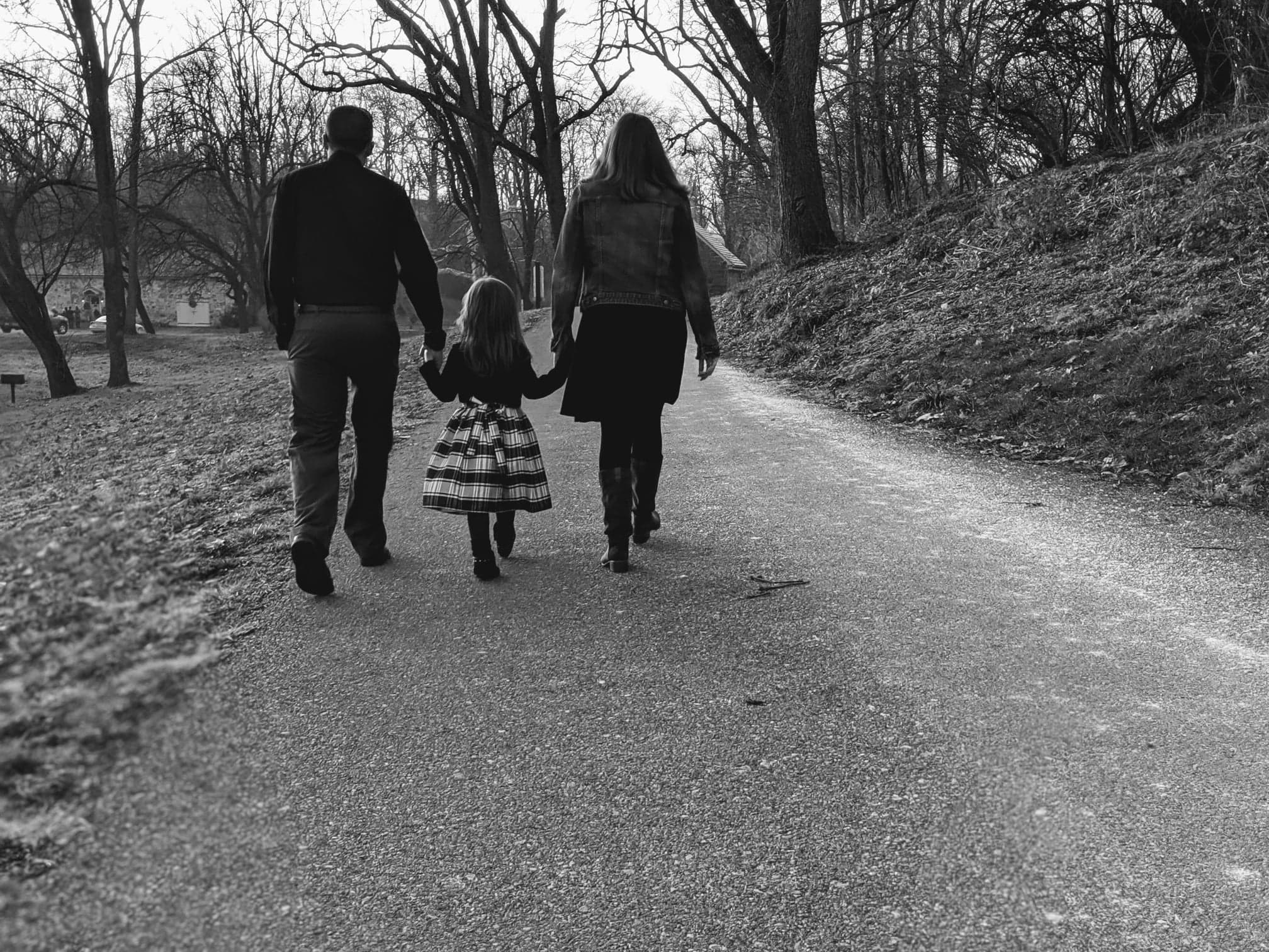 Little girl holding hands and walking with mom and dad on each side, black-and-white photo