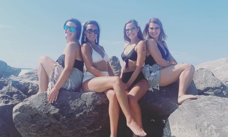Four friends at the beach smiling