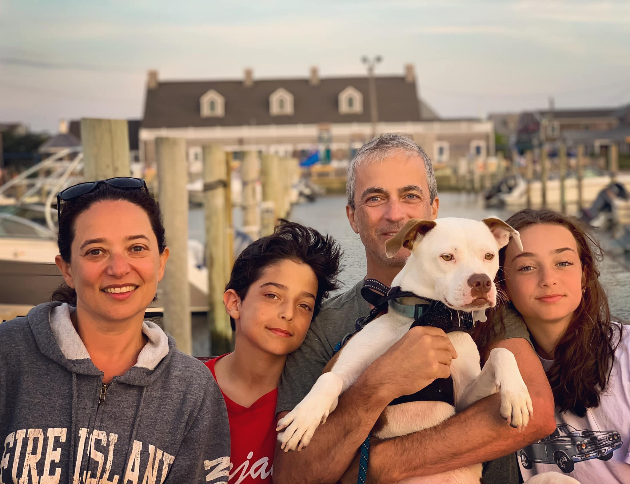 Family with their dog on a pier, color photo