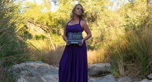 Woman standing on rocks holding sign love shouldn't hurt