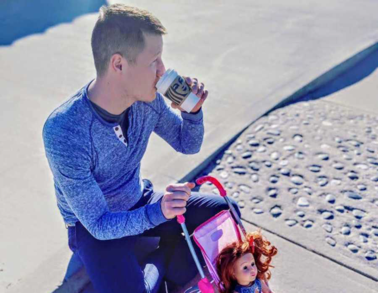 Dad with doll in stroller drinking coffee