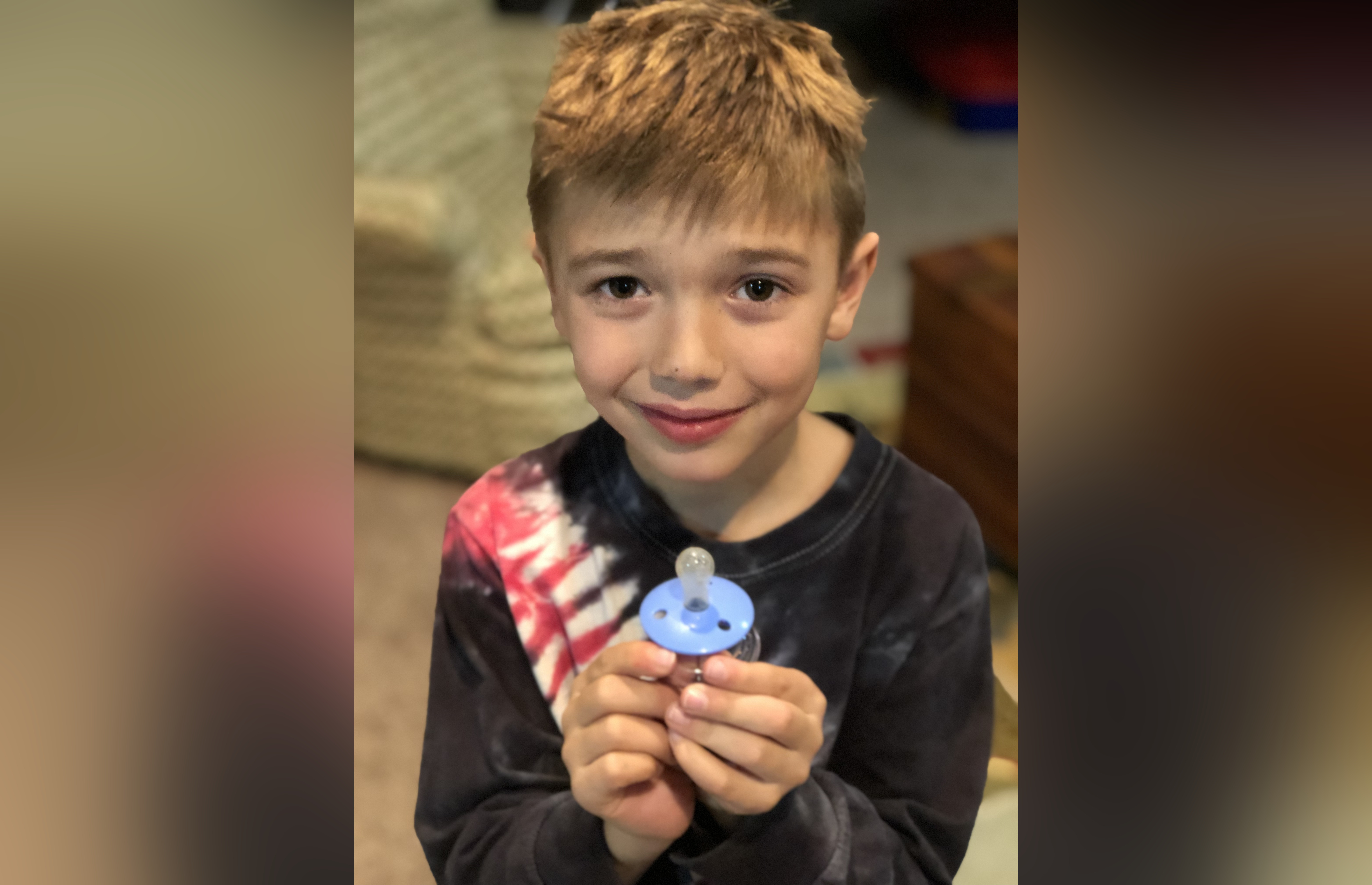 Little boy holding blue pacifier