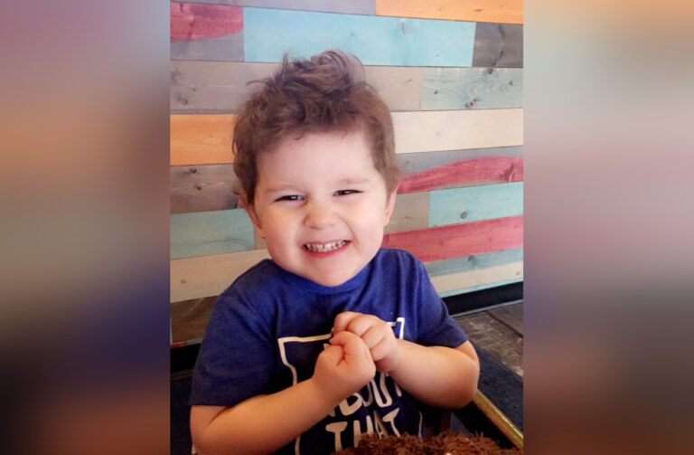 Little boy in high chair smiling