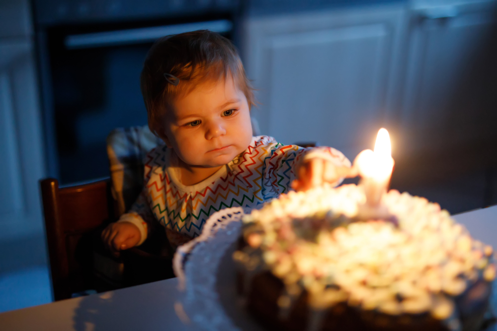 Toddler with first birthday cake and candle