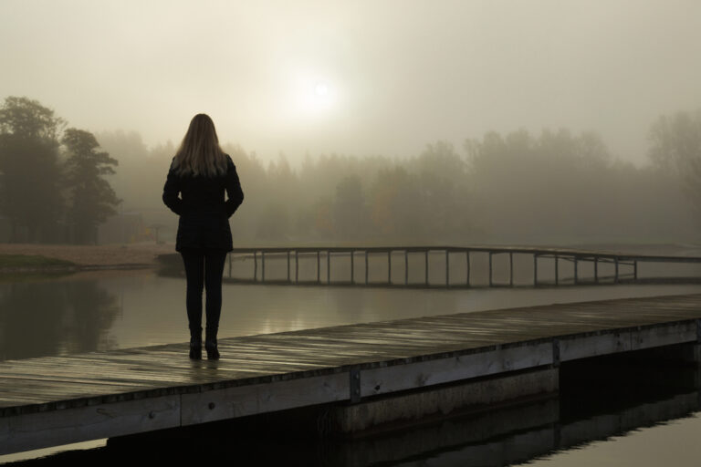 Woman standing alone on dock