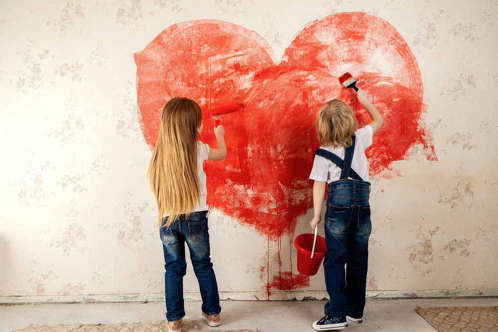 Kids painting a red hart on wall