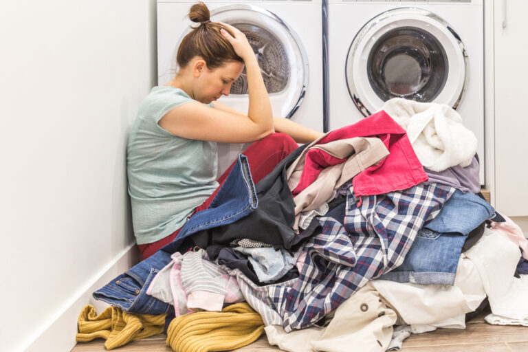 Woman with head down sitting in laundry pile