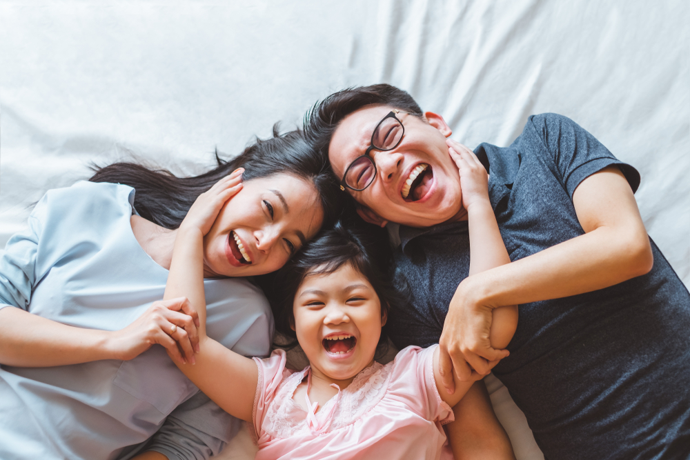Family laughing together on bed at home