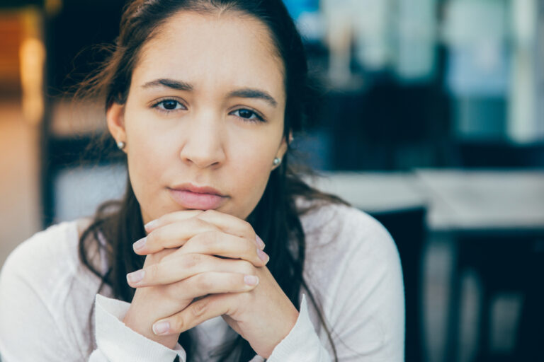 Woman looking at camera with hands clasped