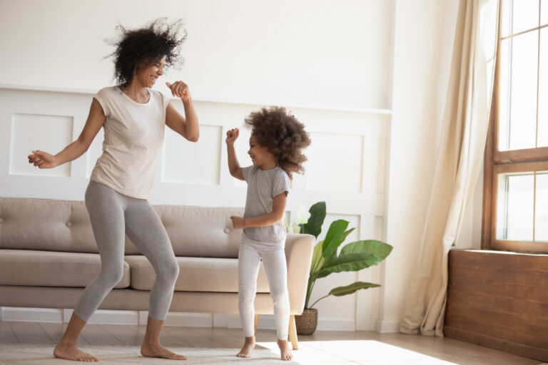 Mother and daughter at home dancing in living room