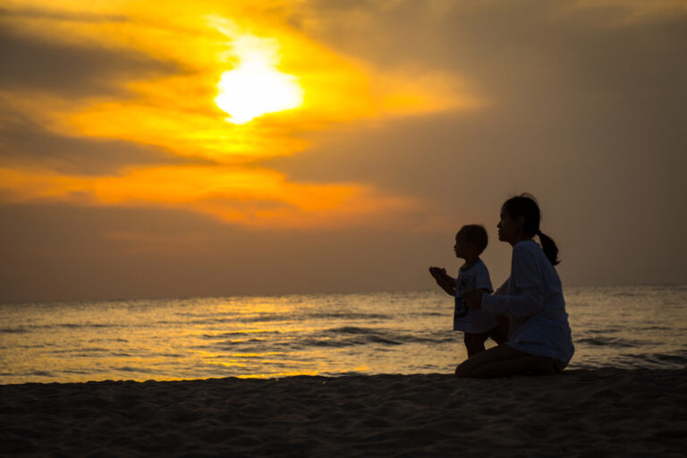 Silhouette of mother and child at the shore at sunset