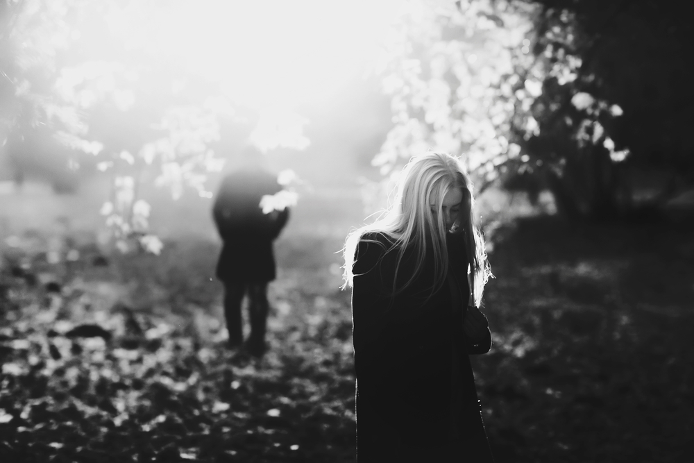 black and white photo of women sad in forest