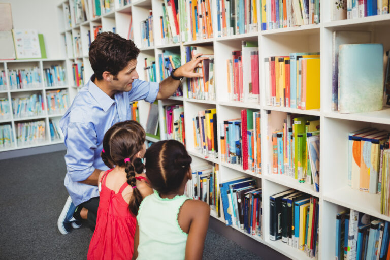 Adult and two children selecting books from a shelf