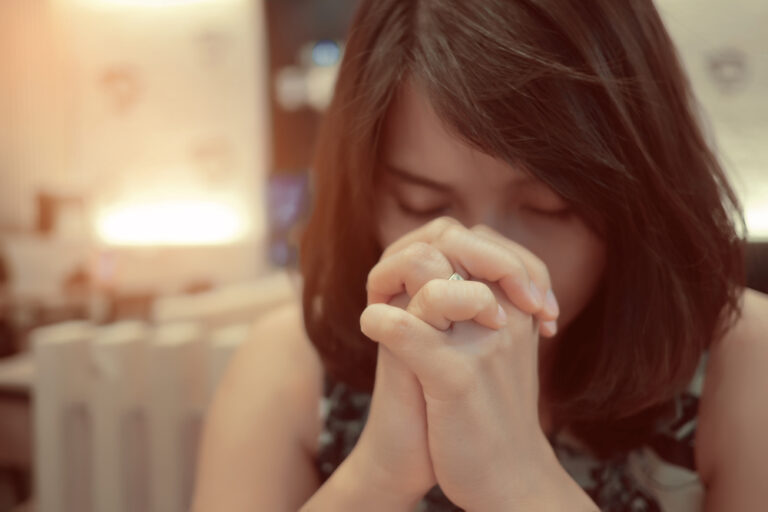 Woman with hands folded in prayer