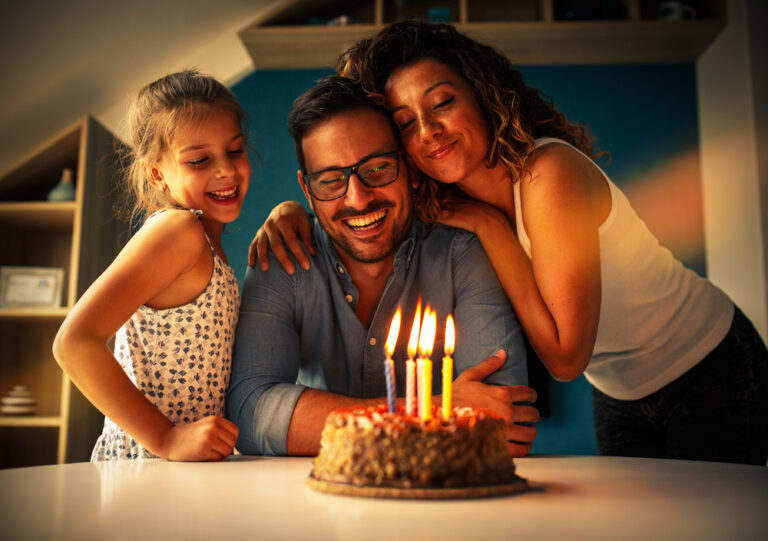 Family of three with birthday cake and candles