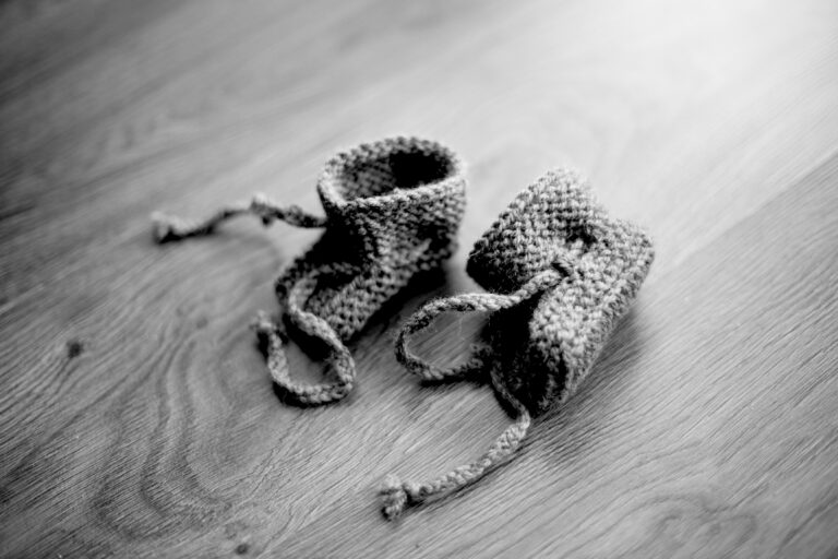 Black and white photo of baby booties on floor