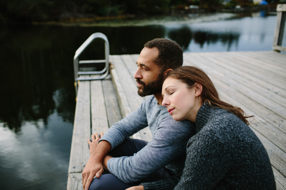 Man and woman sitting on end of dock by water