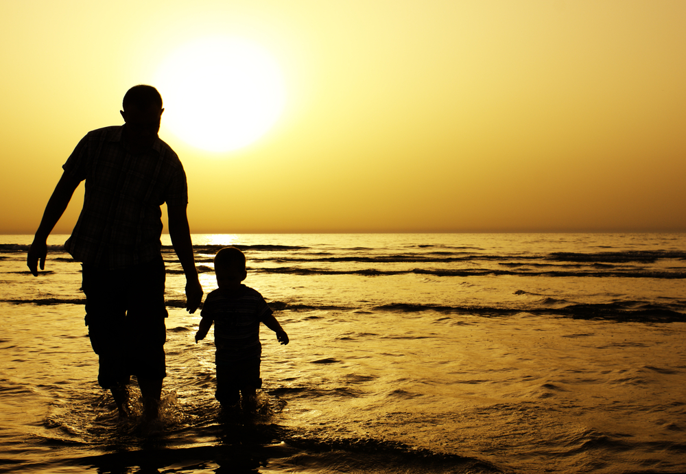 Man and child in ocean at sunset