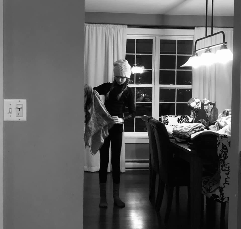 Teen girl folding laundry black and white photo