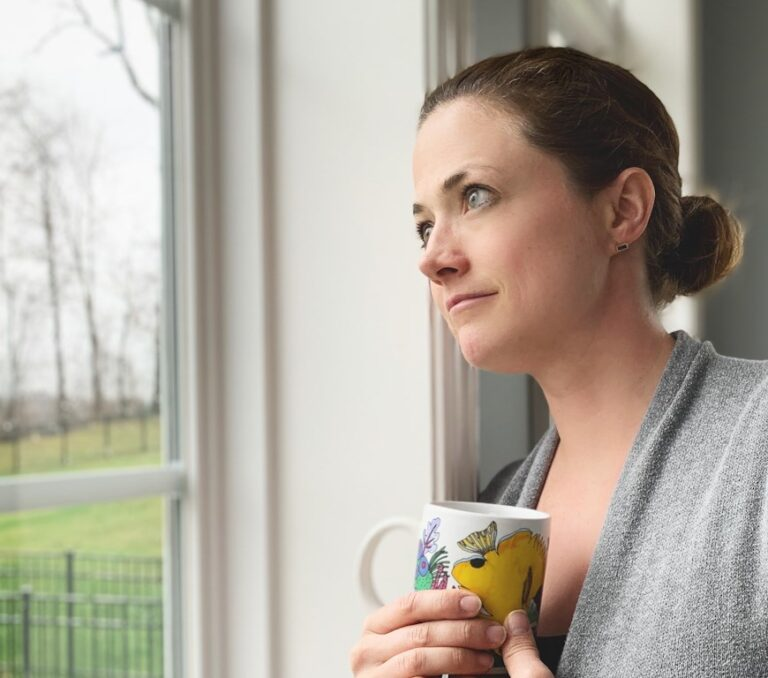 Woman holding coffee mug looking out window