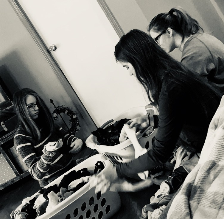 Three girls folding laundry together, black-and-white photo