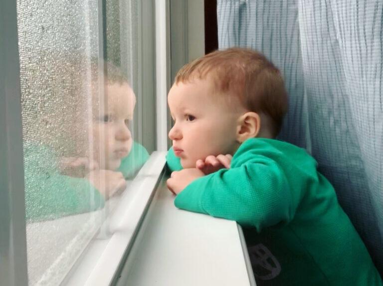 Little boy looking out rainy window