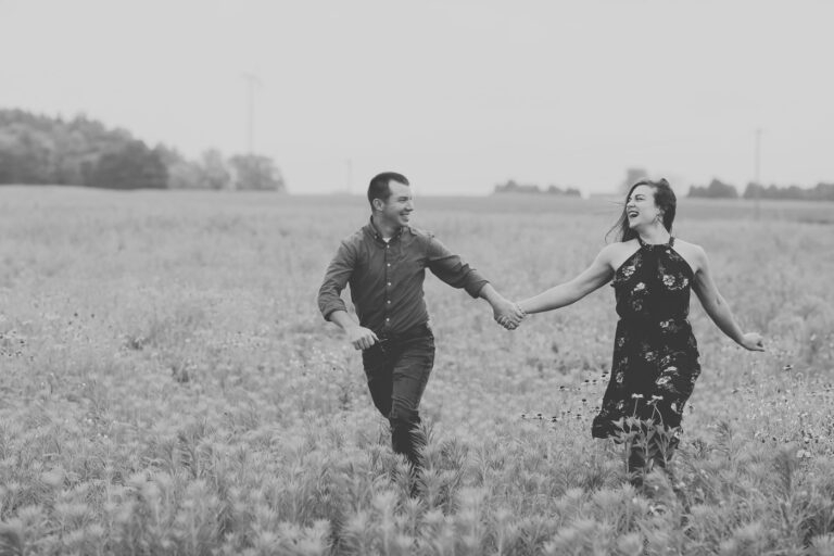 Man and woman holding hands, running in field, black-and-white photo