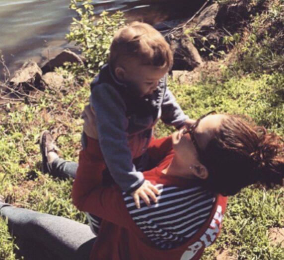 Mom holding little boy near lake edge, color photo