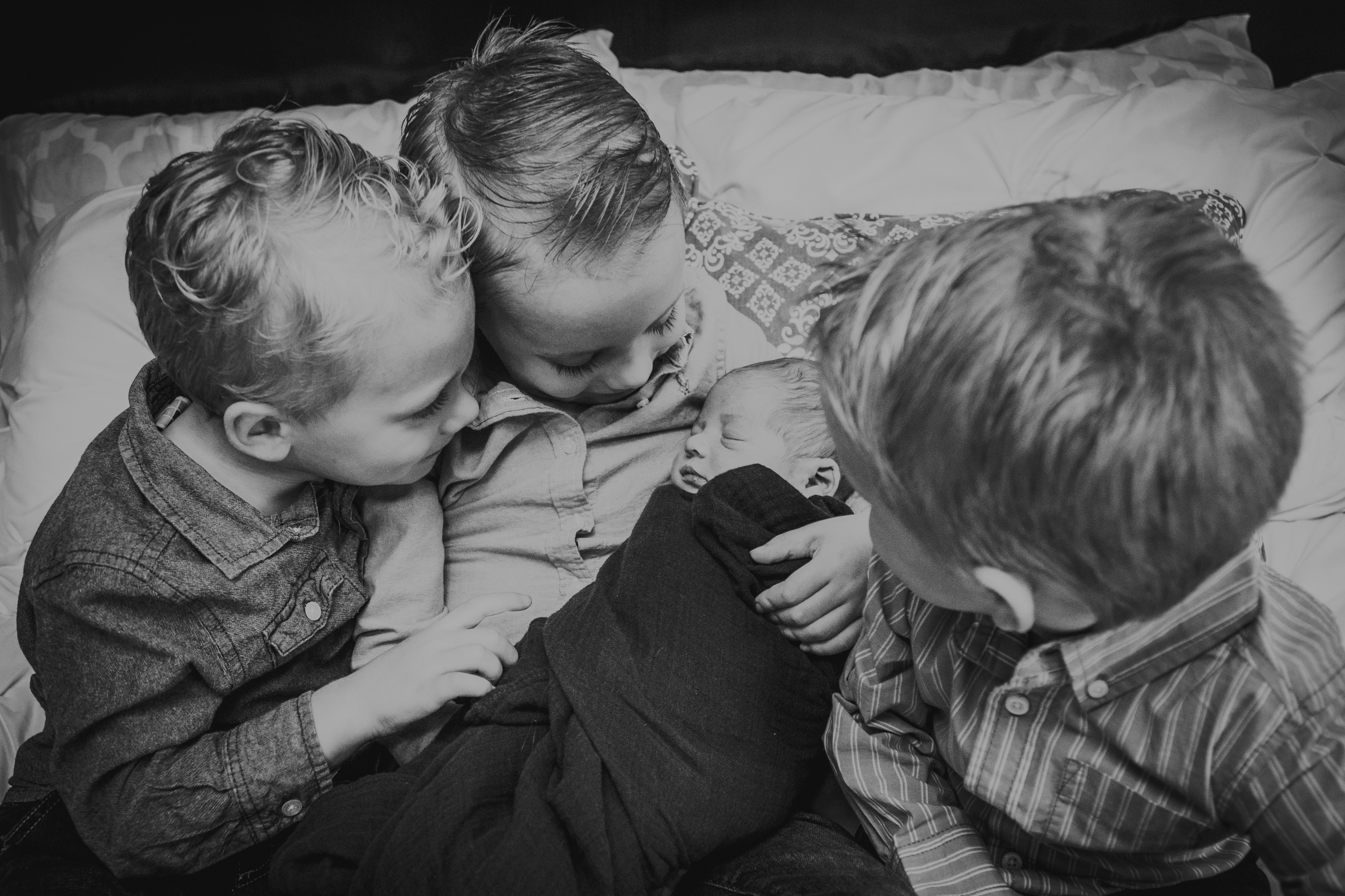 Three big brothers holding and looking on at newborn, black-and-white photo