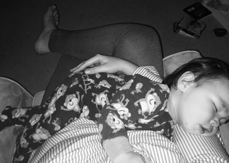 Baby sleeping on mother's lap, black-and-white photo