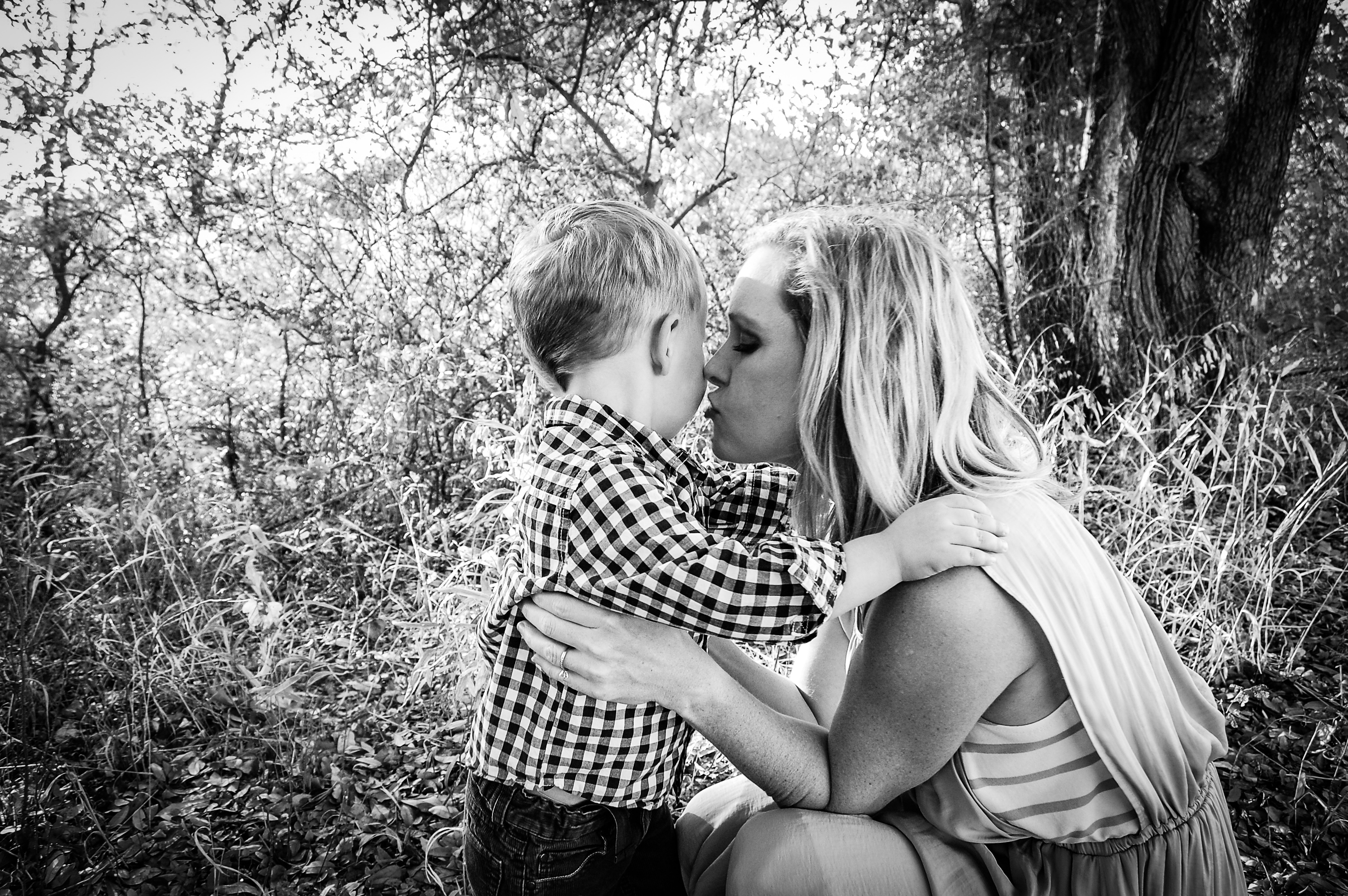 Mother kissing her little boy, black-and-white photo