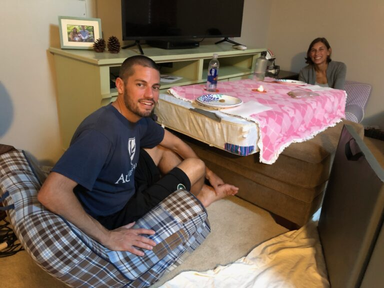 Husband and wife seated at makeshift table made of a crib mattress, color photo