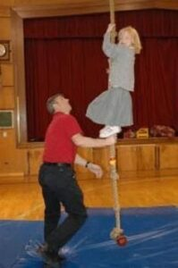 Girl climbing rope at school