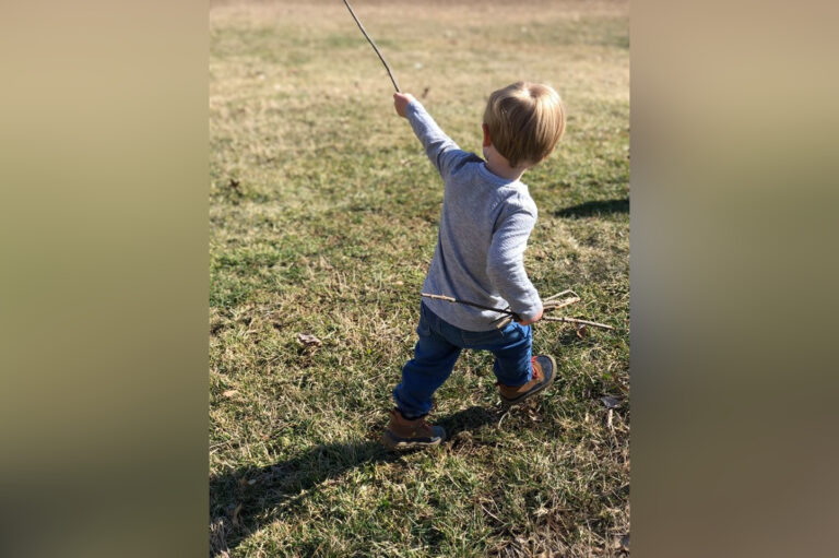 Little boy playing with stick