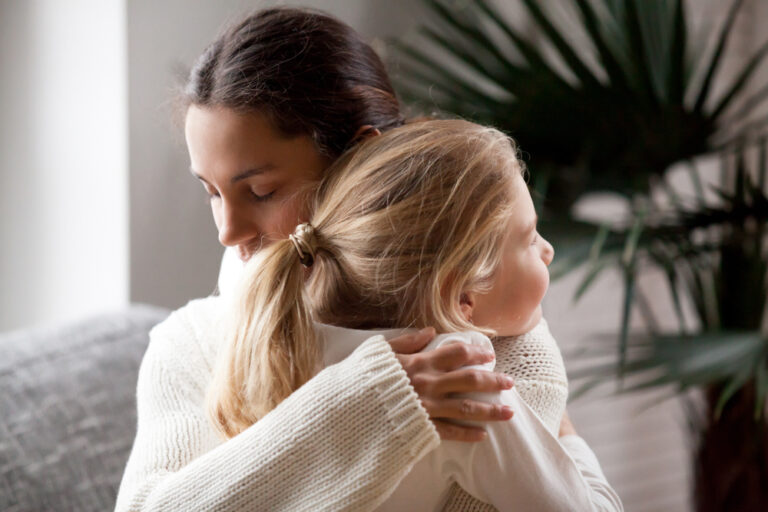 Mother hugging young girl