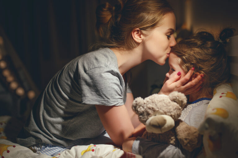 Mother kissing child at bedtime