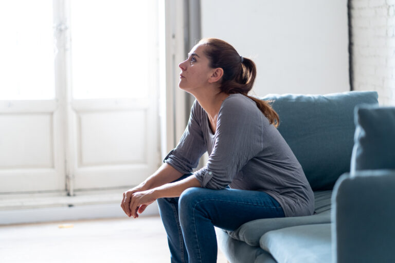 Woman sitting on couch looking up sad
