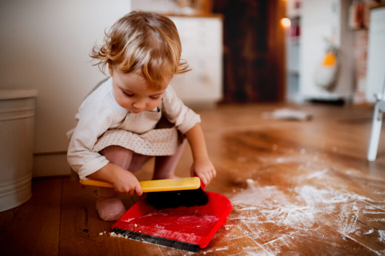Toddler sweeping up dust at home