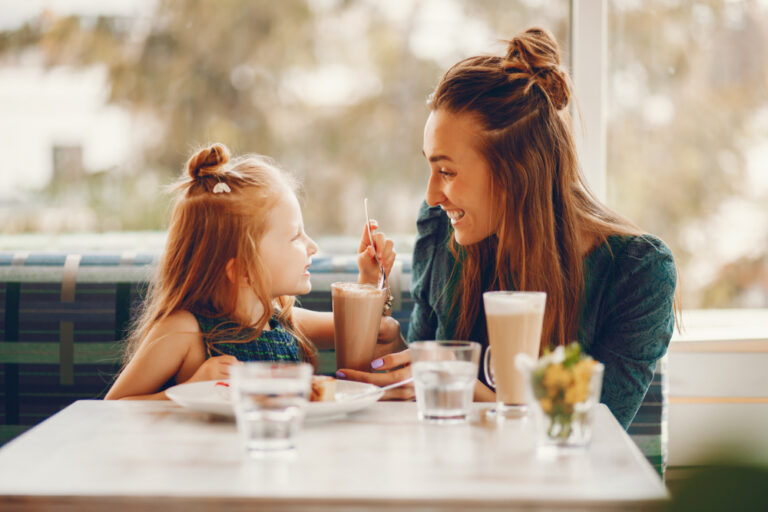 Mother and daughter share milkshakes