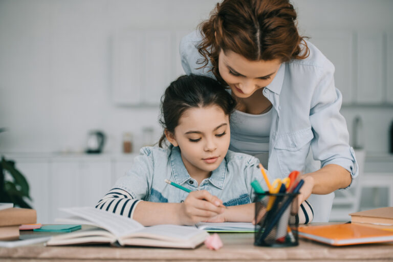 Young child doing school work with woman teacher