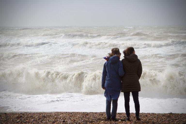Two women watching waves crash