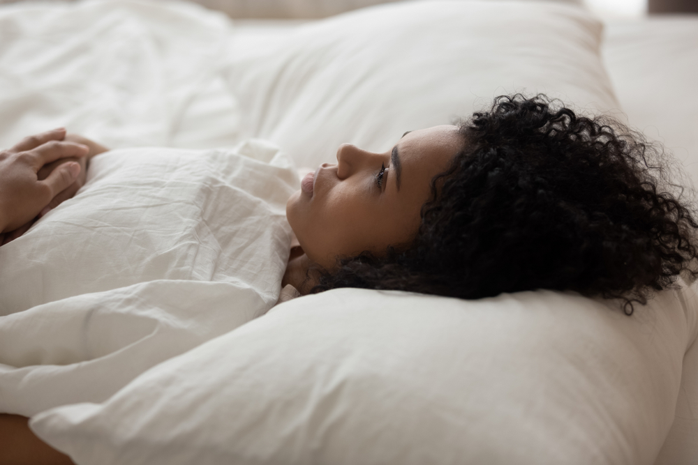 Woman in bed staring at ceiling