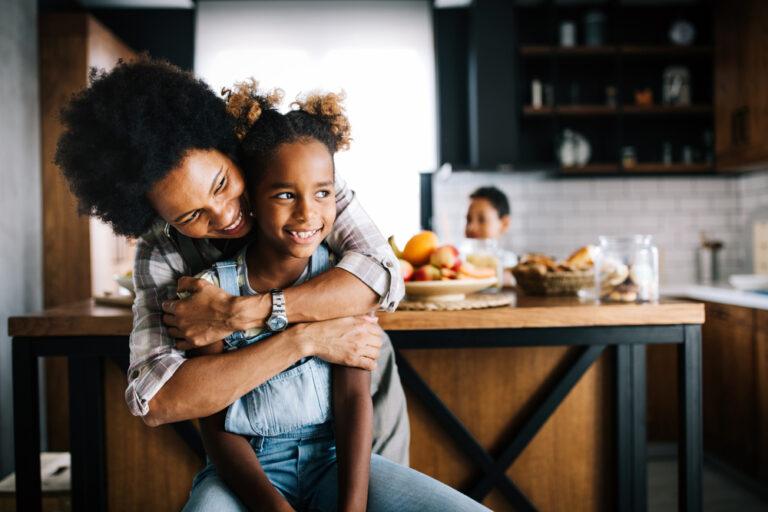 Mom hugging daughter at home