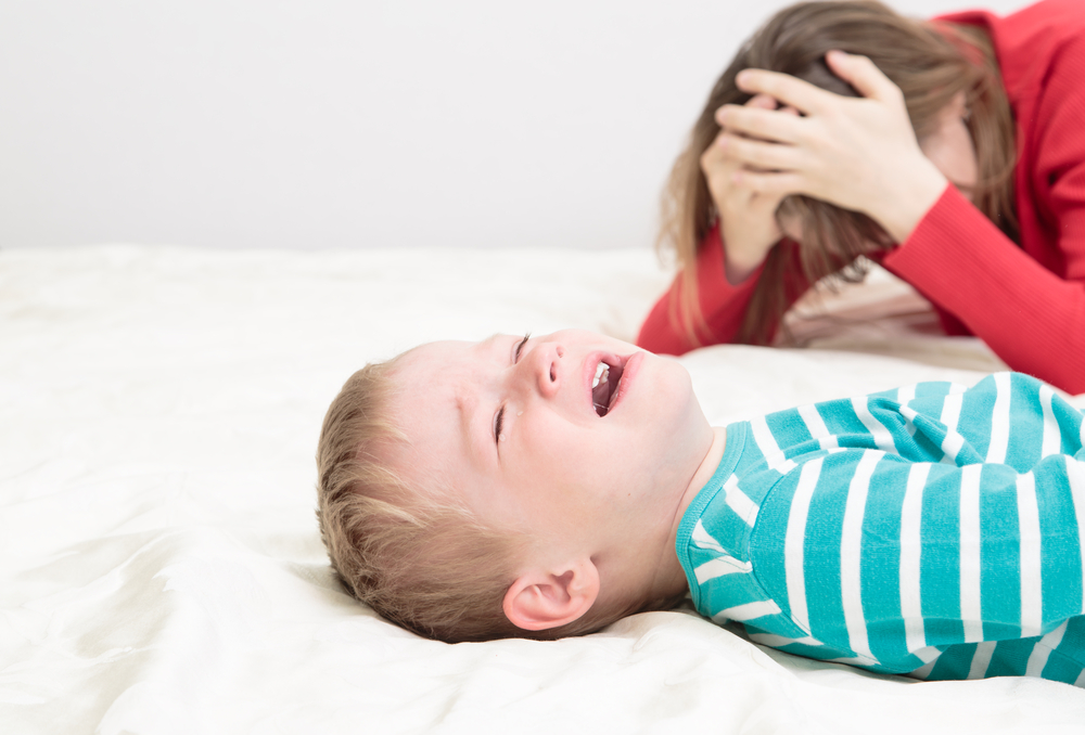 Mom with head in hands as toddler cries