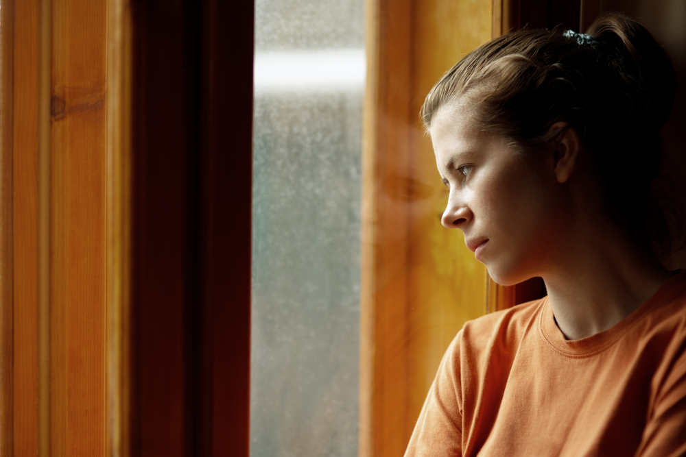 Woman looking out window sad