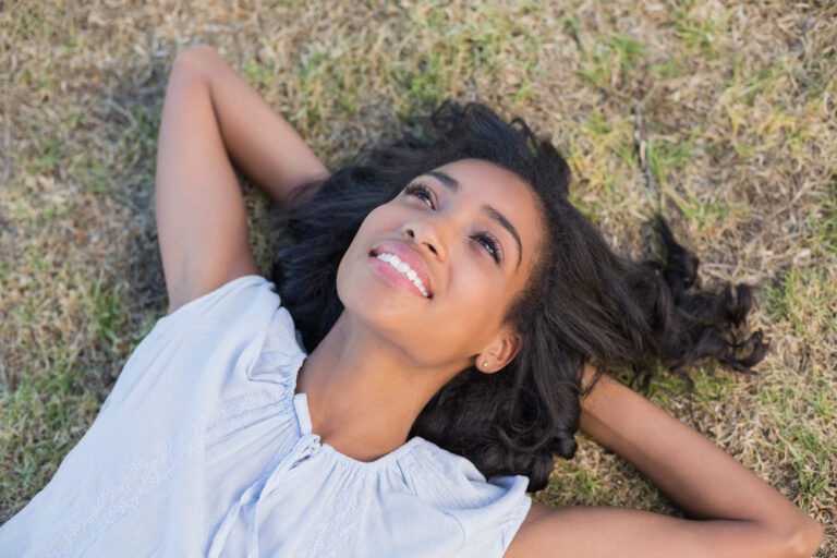 Woman smiling in grass with hands behind her head