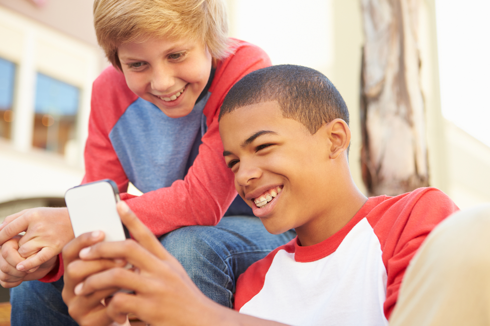 Two tween boys looking at smartphone